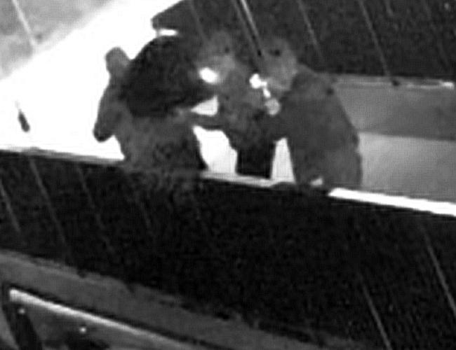 Chuligańskie zrzucenie telewizora z mostka zakochanych. troje mężczyzn na moście trzyma telewizor przed wrzuceniem do kanałku