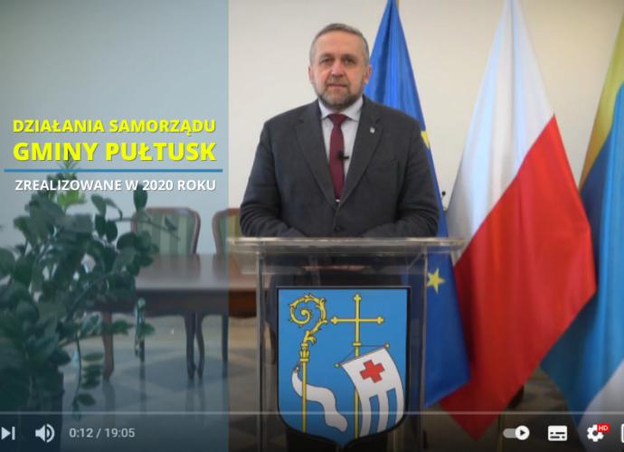 DZIAŁANIA SAMORZĄDU GMINY PULTUSK. Burmistrz stoi przy mównicy. Za burmistrzem flaga unii europejskiej, Polski, i Pułtuska. Po prawej stronie napis dzialania samorządu gminy Pułtusk
