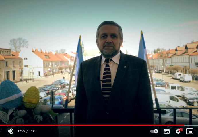 Burmistrz Miasta Pułtusk składa zyczenia mieszkańcom przed kamerą. Stoi na balkonie urzędu. Za min w tle powiewają flagi miasta i rozciąga sie widok na panoramę rynku
